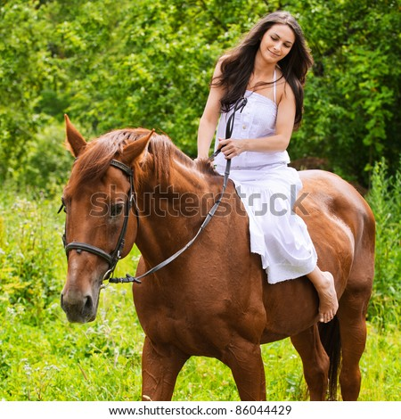 Portrait of young beautiful brunette woman wearing white dress riding dark horse at summer green forest. - stock photo