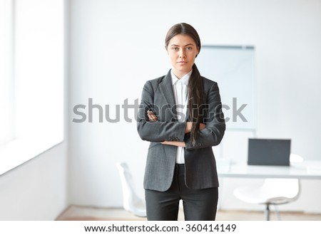 Portrait of young beautiful business woman in the office. Crossed arms.