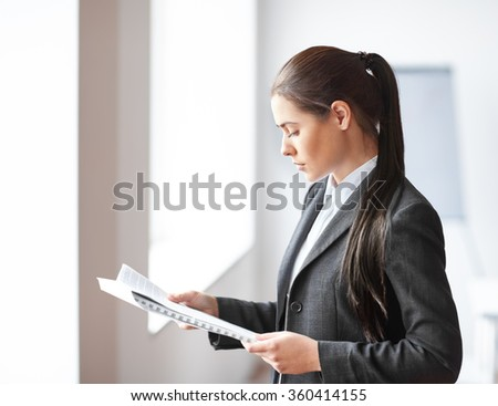 Portrait of young beautiful business woman reading documents in the office - stock photo