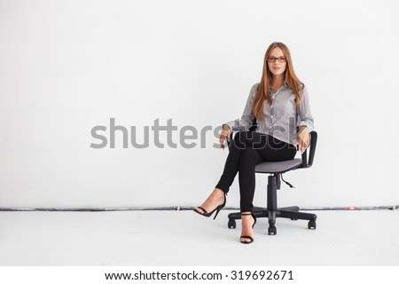 Portrait of young beautiful business woman sitting on chair against white wall. - stock photo