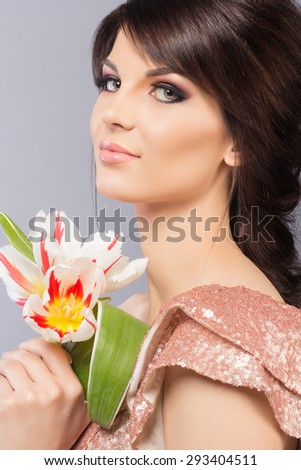 Portrait of young beautiful caucasian brunette in gorgeous dress with flowers on grey bacwthkground - stock photo