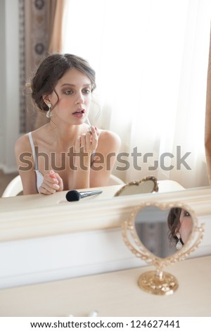 Portrait of young beautiful caucasian woman sitting in front of the mirror and putting on lip gloss - stock photo