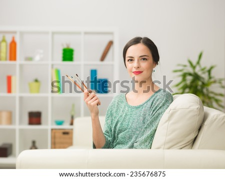 portrait of young beautiful caucasian woman sitting on sofa at home, holding paintbrushes and smiling - stock photo