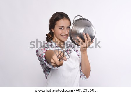 Portrait of young beautiful chef pointing to camera with a whisk. Isolated white background.