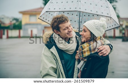 Portrait of young beautiful couple embracing and laughing under the umbrella in an autumn rainy day. Love and couple relationships concept. - stock photo