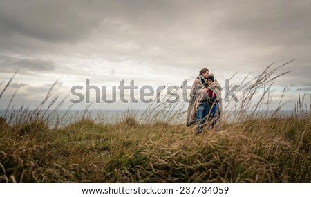 Portrait of young beautiful couple embracing under blanket in a cold day with sea and dark cloudy sky on the background - stock photo