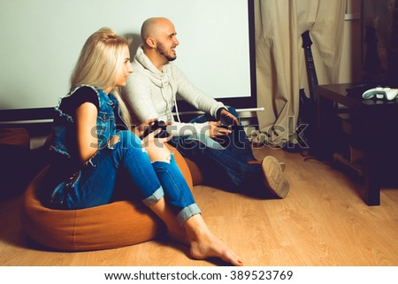 Portrait of young beautiful couple having fun and playing games. concept of leisure entertainment and fun - stock photo