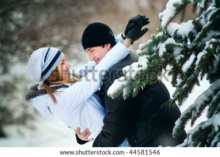 Portrait of young beautiful couple in winter park.