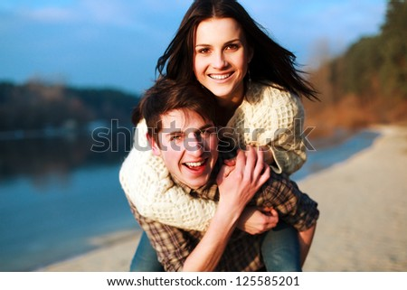 Portrait of young beautiful couple running on the beach. Happy joyful boy and girl, spring weather. - stock photo