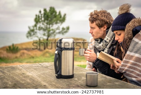 Portrait of young beautiful couple under blanket reading book in a cold day with sea and dark cloudy sky on the background - stock photo