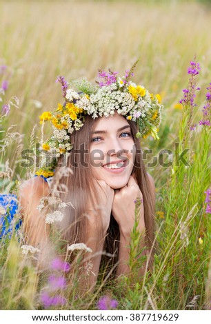 Portrait of young beautiful cute romantic  girl wearing a wreath of wild flowers in summer day, outdoors. Happy woman. Series of photos - stock photo