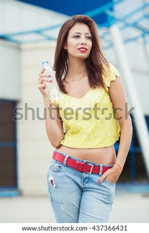 Portrait of young beautiful dark-haired woman wearing trendy knitted vintage t-shirt standing with bottle of water on the street. Modern urban background. Outdoor shot