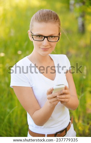 Portrait of young beautiful fair-haired woman wearing white dress looking at telephone at summer green park. - stock photo
