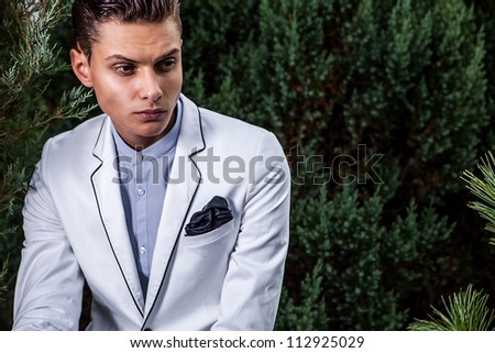 Portrait of young beautiful fashionable man against autumn garden. - stock photo