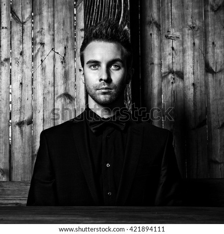Portrait of young beautiful fashionable man against wooden wall In black suit & bow tie. Black-white fashion photo against wooden background. - stock photo