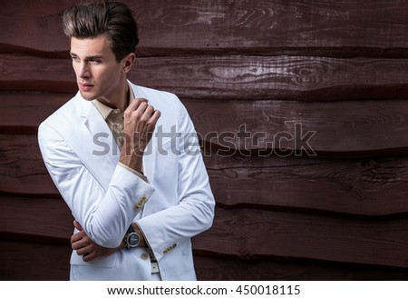 Portrait of young beautiful fashionable man in white costume against wooden wall. - stock photo