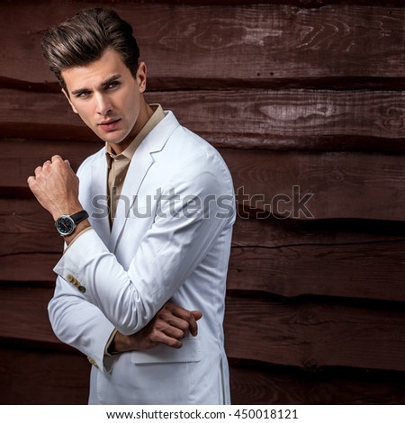 Portrait of young beautiful fashionable man in white costume against wooden wall.