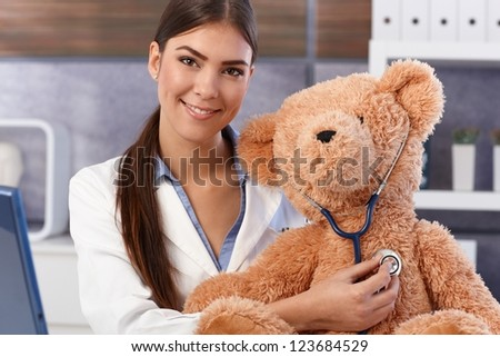Portrait of young beautiful female doctor examining soft toy with stethoscope. - stock photo