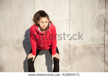 Portrait of young beautiful female leaning on gray wall while resting after everyday practice. Woman athlete jogger taking a break and listening music. Sport active lifestyle concept. Copy space