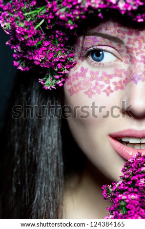 Portrait of young beautiful fresh girl's half face with stylish make-up and pink flowers