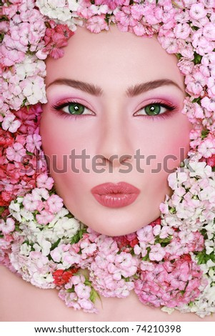 Portrait of young beautiful fresh girl with stylish make-up and pink flowers around her face - stock photo