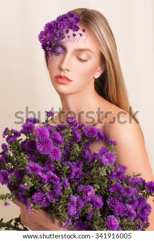Portrait of young beautiful fresh girl with stylish make-up and purple flowers around her face and hair.