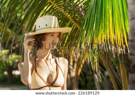 Portrait of young beautiful girl at tropical beach for vacation, looking away from camera - stock photo