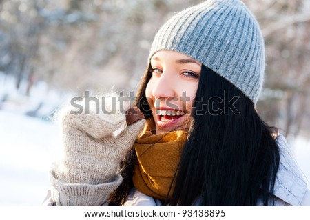 Portrait of young beautiful girl having fun outdoors in winter forest and eating tasty chocolate candy - stock photo