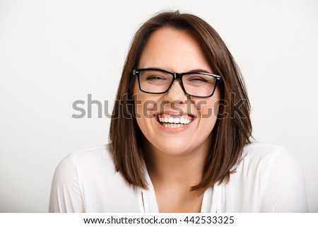 Portrait of young beautiful girl in glasses playing ape, laughing over white background.