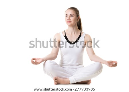 Portrait of young beautiful girl in white sportswear doing yoga practice, sitting cross-legged in sukhasana (Easy Pose), front view, studio shot, isolated - stock photo