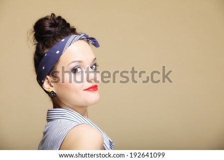 Portrait of young beautiful girl retro style fancy make-up hair bun brown background