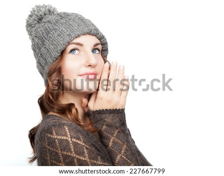 Portrait of young beautiful girl with blue eyes and fresh clean skin in grey winter hat and sweater is dreaming and smiling over white background. Close up. Cope space. Isolated. - stock photo