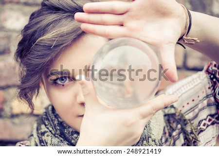 Portrait of young beautiful girl with blue eyes balancing a crystal ball on the hand - Woman performing contact juggling  - stock photo