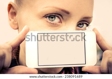 Portrait of young beautiful girl with blue eyes holding a smart phone - Blank phone screen and pretty model - stock photo