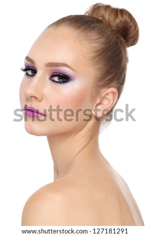Portrait of young beautiful girl with fancy make-up and hair bun, on white background