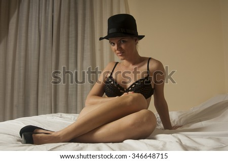 portrait of Young beautiful girl with long legs wearing black bra hat and high heels shoes posing on the bed looking straight at the camera - stock photo