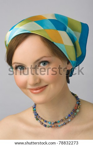 Portrait of young beautiful girl with naked shoulders, with kerchief on head and with costume jewellery - stock photo