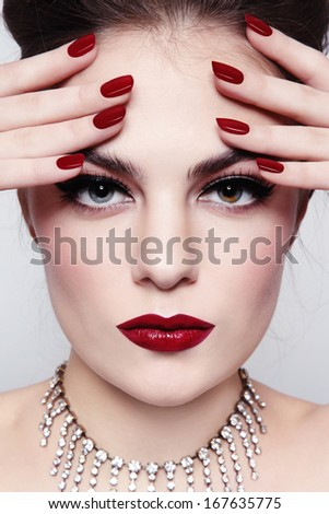 Portrait of young beautiful girl with red lips and manicure