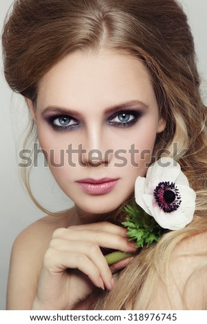 Portrait of young beautiful girl with stylish violet smoky eyes make-up and messy hairdo - stock photo