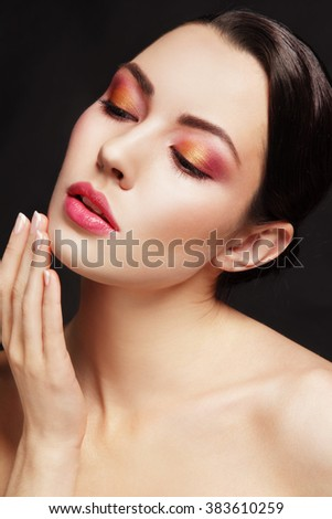 Portrait of young beautiful glamorous woman with stylish make-up touching her face