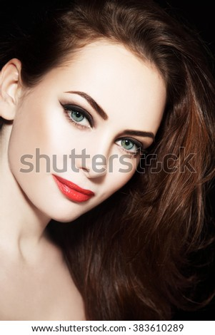 Portrait of young beautiful grren-eyed woman with winged eyes make-up and red lipstick - stock photo