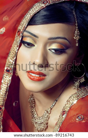 Portrait of young beautiful happy indian bride with bright makeup and golden jewelry - stock photo
