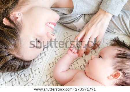 Portrait of young beautiful happy mother and her cute sweet little newborn baby girl playing and lying on woolen blanket on the bed at home. Mother holding her baby's hand gently with love.   - stock photo