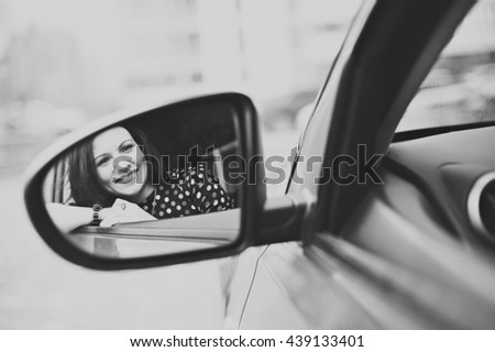 Portrait of young beautiful happy woman in the reflection of the car mirror, close-up, black-and-white image. - stock photo