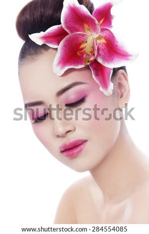 Portrait of young beautiful healthy asian girl with radiant skin and pink lily in her hair over white background  - stock photo