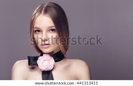 Portrait of young beautiful healthy woman with fancy pink rose on a strip over her neck. - stock photo