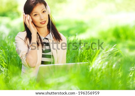 Portrait of young beautiful hipster girl in stylish trendy jacket sitting in green grass and using laptop computer with headphones. White shiny smile. Close up. Copy-space. Outdoor shot - stock photo