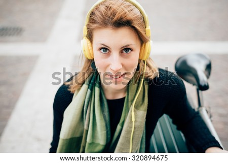 Portrait of young beautiful hipster sporty blonde woman sitting on a bench, looking in camera, smiling, listening music with headphones - music, relaxing concept