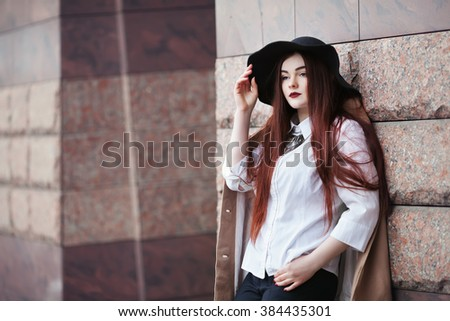 Portrait of young beautiful lady wearing stylish classic clothes posing at street of the old city. Girl looking forward. Plus size model. Female fashion concept. Close up. Copy space. Toned - stock photo