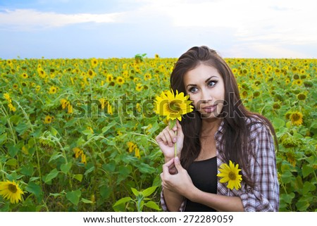 Portrait of Young beautiful latin girl walk in sunflower field background Space for inscription Cute slim woman in sunny summer day against sky Brunette woman in agriculture meadow hold yellow flower - stock photo